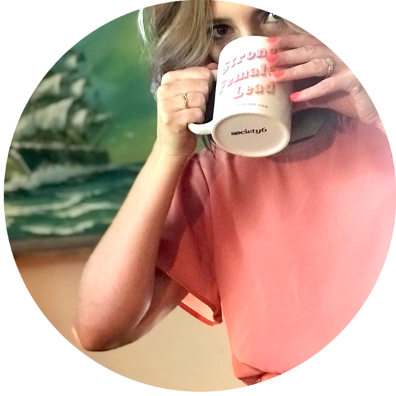 Woman drinking from coffee mug that reads strong female lead